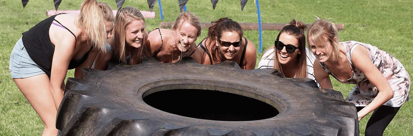 Group of Hens moving a large tyre during a Mini Highland Games in Edinburgh at Great Away Days