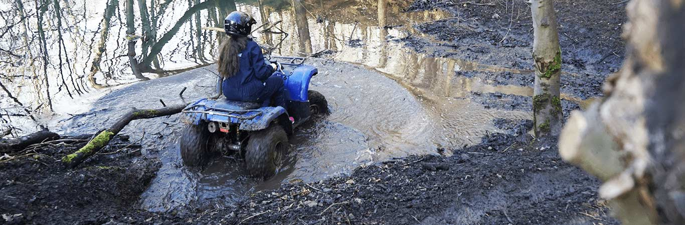 Woman on hen party on a Quad in a puddle in the middle of Great Away Days in Edinburgh