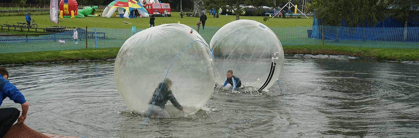 Two kids playing in water walkers on their fun away day in Scotland with great away days