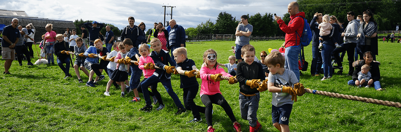 Kids on a fun away day doing a tug of war during a mini highland games in Edinburgh