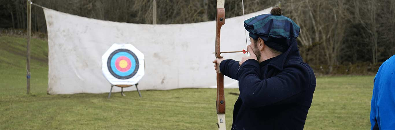 Man on a Stag Do in a Scottish Hat shooting an arrow at the target at Great Away Days in Edinburgh