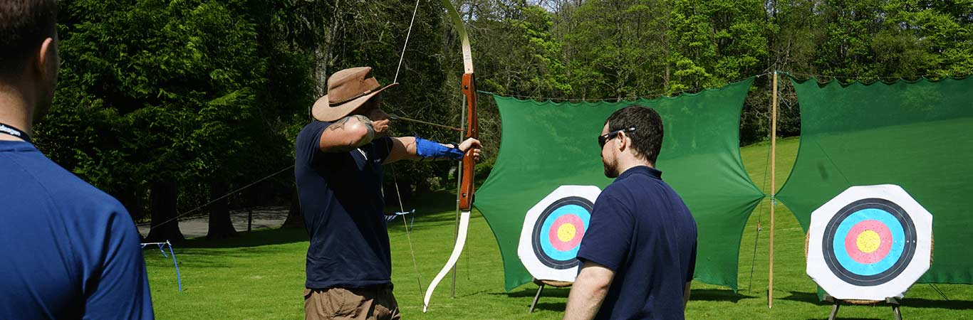 Man with a hat ready to shoot his bow to the target on a team away day in Edinburgh with Great Away Days