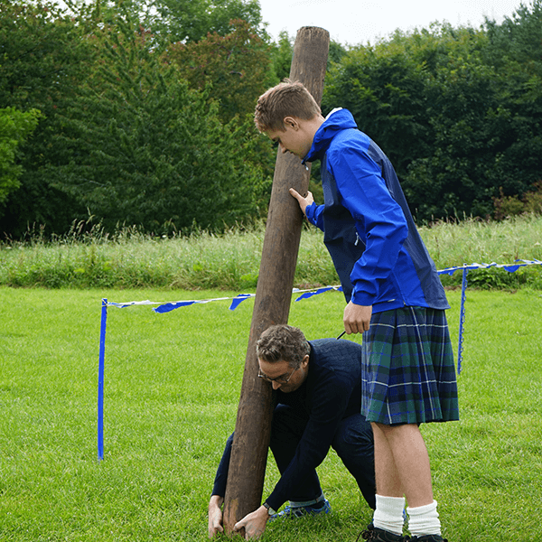 Great Away Days Freelancer helping a man doing caber toss in a Mini Highland Games