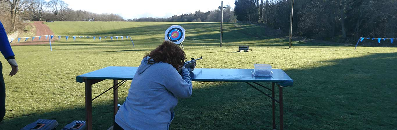 A woman at a Hen Party ready to take a shot at target during Air Rifle Shooting in Edinburgh at Great Away Days