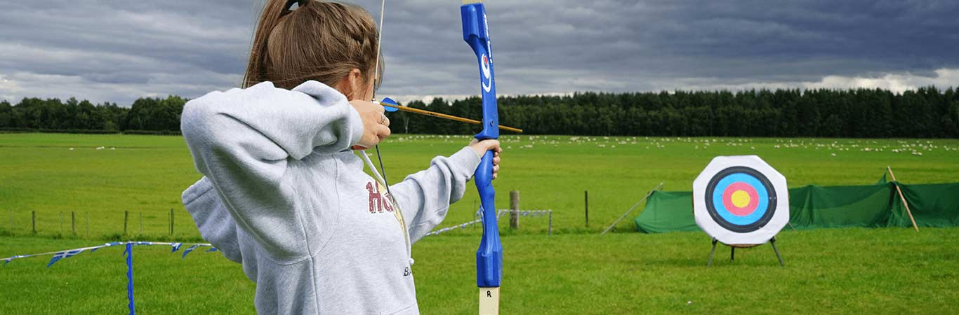 Girl on her fun away day getting ready to shoot the arrow at the target with great away days