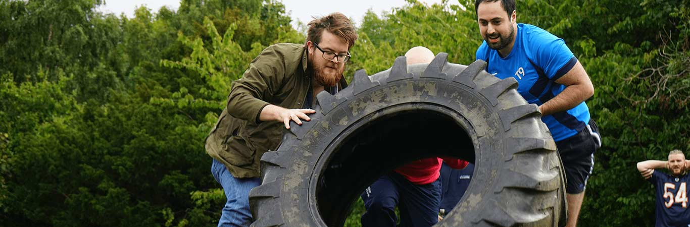Stag Group in Edinburgh flippin a tyre during a Mini Highland Games with Great Away Days
