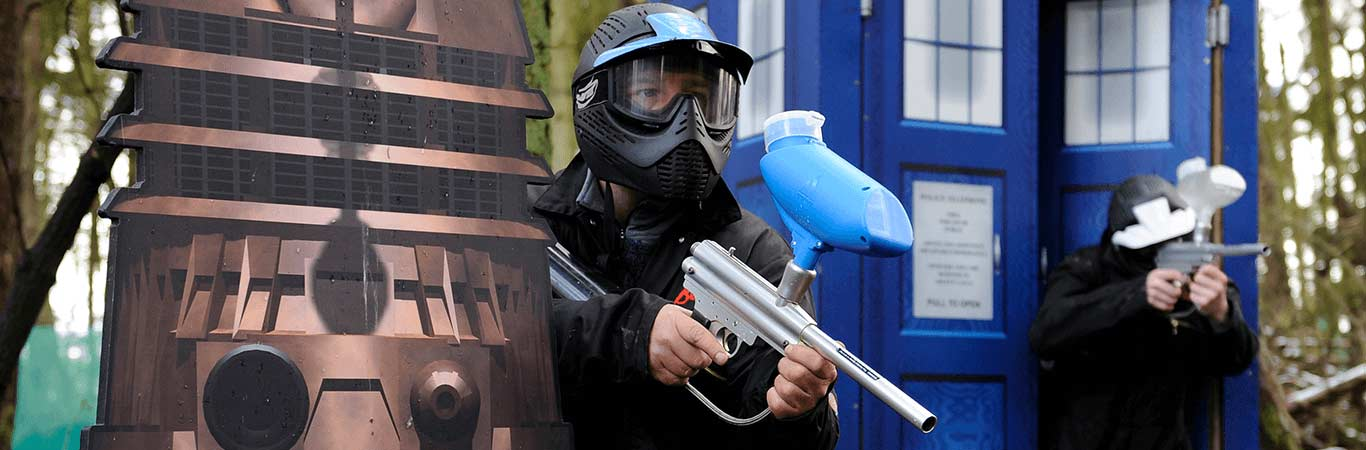 Two people ready to shoot paintballs next to a tardis, perfect for your hen do in Edinburgh with Great Away Days